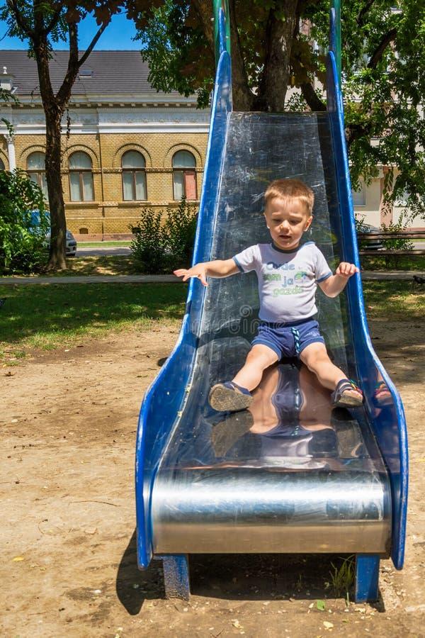 Pojken tycker om att gå ner glidbanan royaltyfri foto