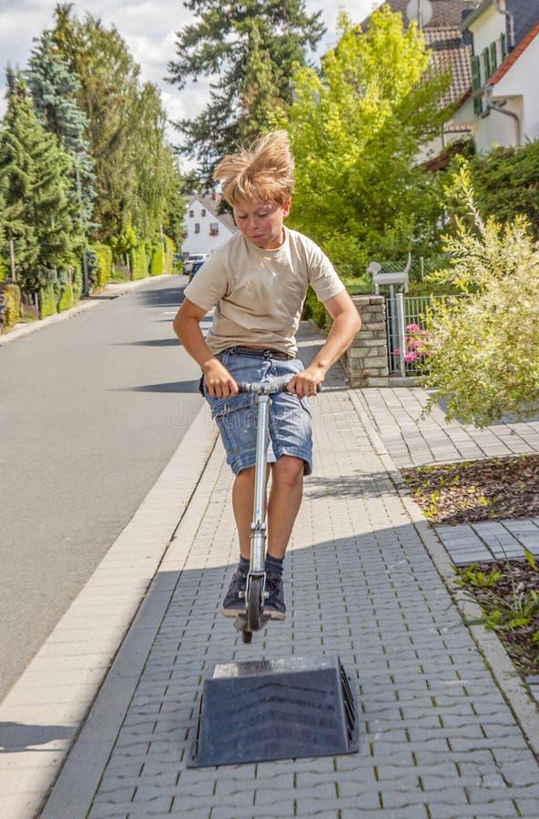 Pojken tycker om att skrika med sin pustskooter på sidpromenaden arkivfoton