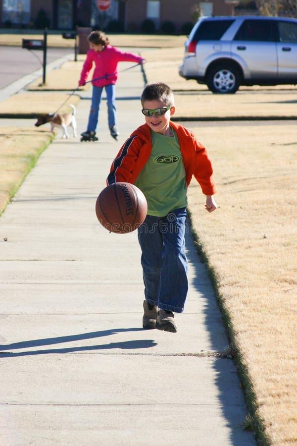 Pojken tycker om att studsa basket ner gatan arkivfoton