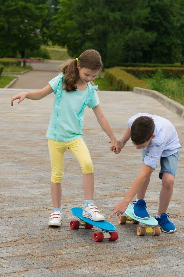Pojken undervisar flickan hur man rider på ett bräde med rullar in en parkera på vägen royaltyfri bild