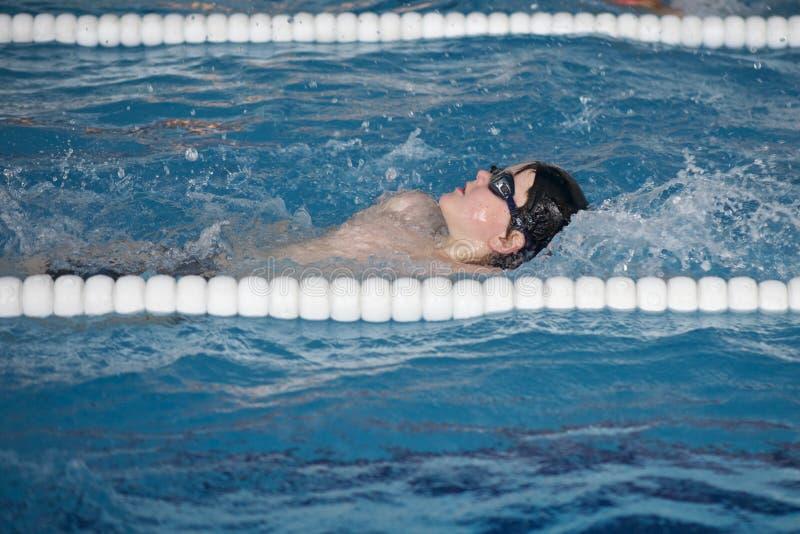 Pojken utbildar i simbassäng, för competen royaltyfria foton