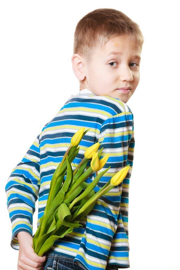 Pojkenederlagbukett av blommor bak honom arkivbild