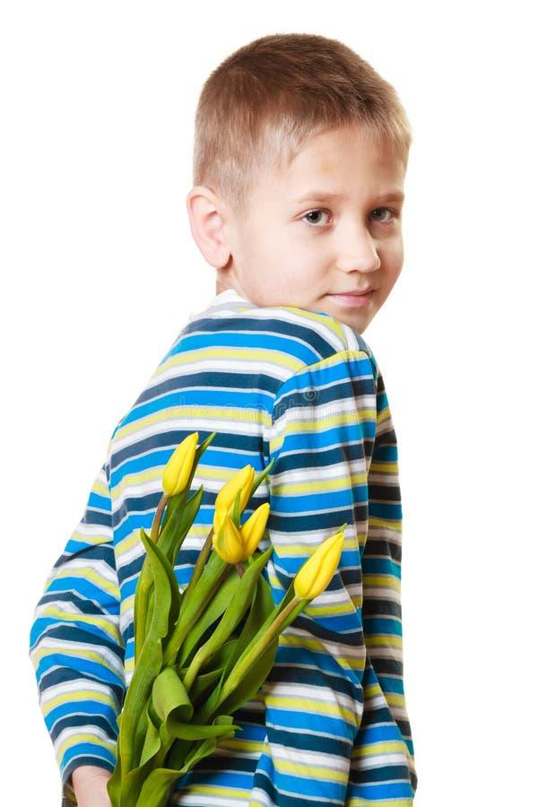 Pojkenederlagbukett av blommor bak honom royaltyfri fotografi