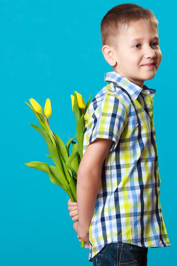 Pojkenederlagbukett av blommor bak honom royaltyfria foton