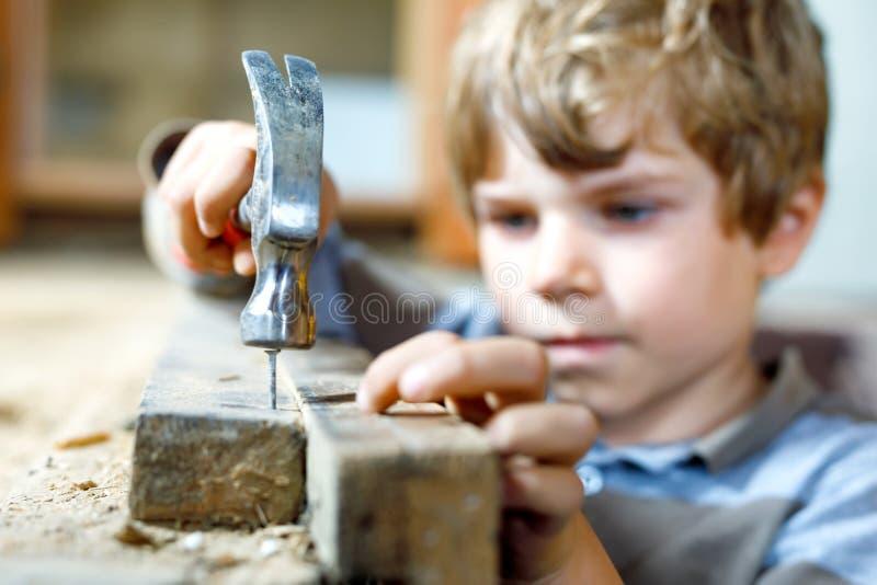 Pojkeportion för liten unge med leksakhjälpmedel på konstruktionsplats Roligt barn av 6 år som har gyckel på byggande av den nya  royaltyfri foto