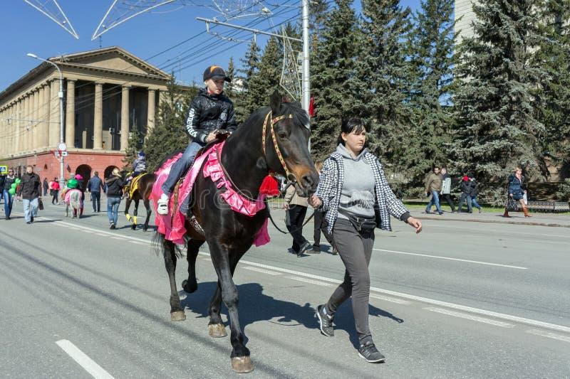 Pojkeritter på en smart brun häst som är drivande vid en flicka längs avenyn av den Krasnoyarsk staden under berömmen av Victory  fotografering för bildbyråer