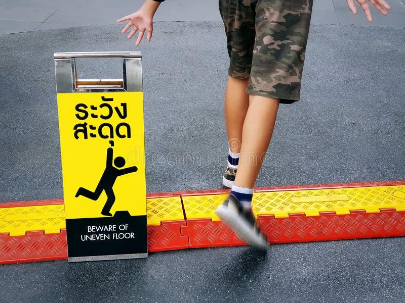 Pojkes lägre avsnitt och att akta sig av den ojämna golvetiketten med engelska och thailändska texter arkivbilder