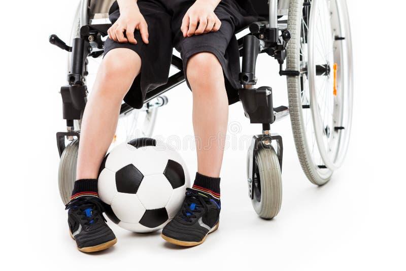 Pojkesammanträde för rörelsehindrat barn på hållande fotbollboll för rullstol royaltyfri foto