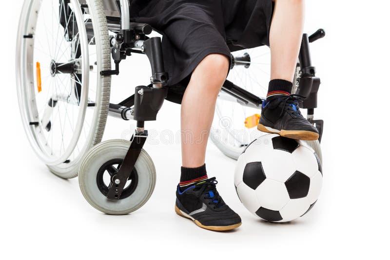 Pojkesammanträde för rörelsehindrat barn på hållande fotbollboll för rullstol fotografering för bildbyråer