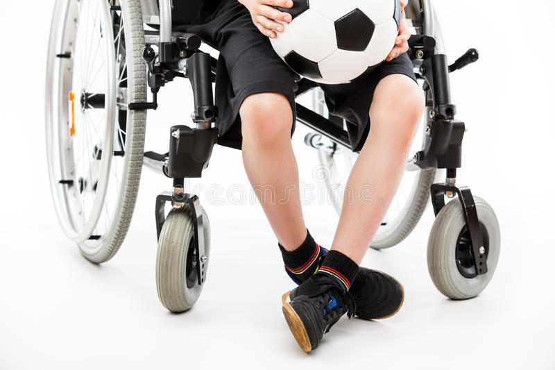 Pojkesammanträde för rörelsehindrat barn på hållande fotbollboll för rullstol royaltyfria foton