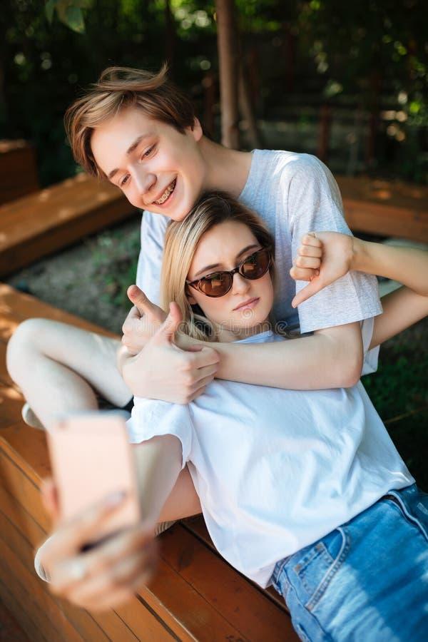 Pojkesammanträde på bänk parkerar in och lyckligt visa upp tummen medan flickan med benägenhet för blont hår på honom och visning royaltyfri bild