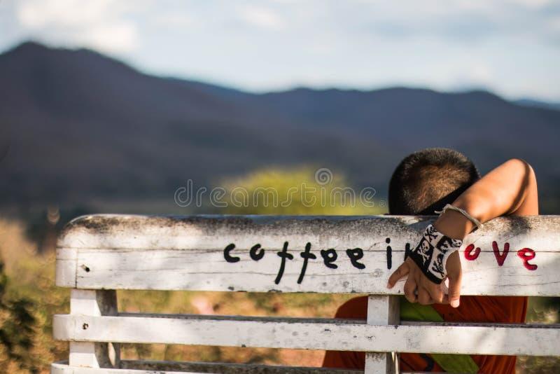 Pojkesammanträde på bänken med bergsikt royaltyfri bild