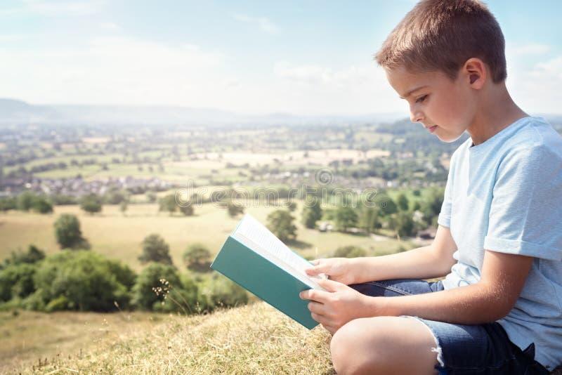 Pojkesammanträde på en kulle som läser en bok i en äng royaltyfri bild