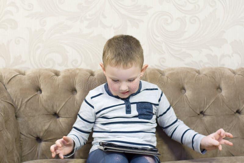 Pojkesammanträde på soffan royaltyfri fotografi