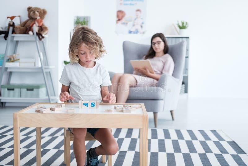 Pojkesammanträde på tabellen och spela med byggnadskvarter medan arkivfoton