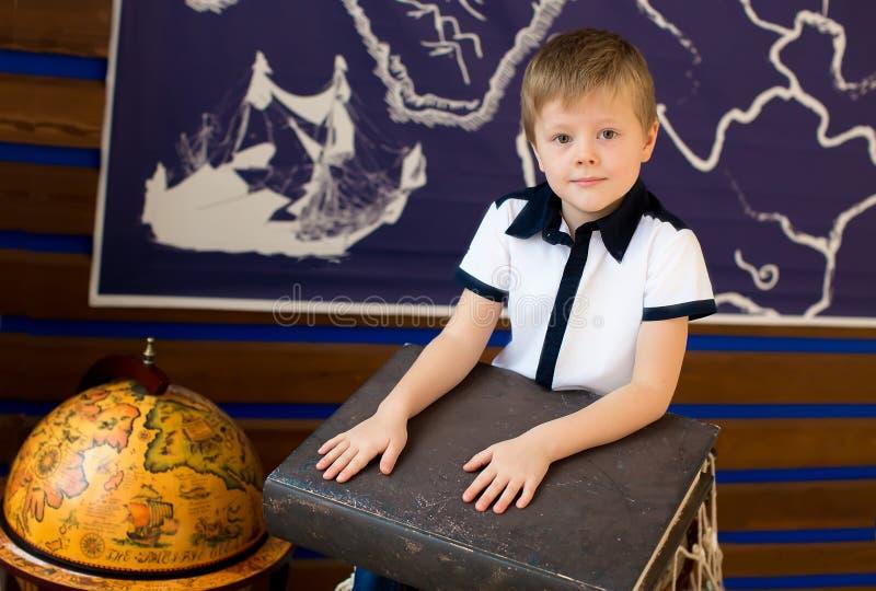 Pojkesammanträdet bredvid jordklotet rymmer en bok royaltyfri fotografi
