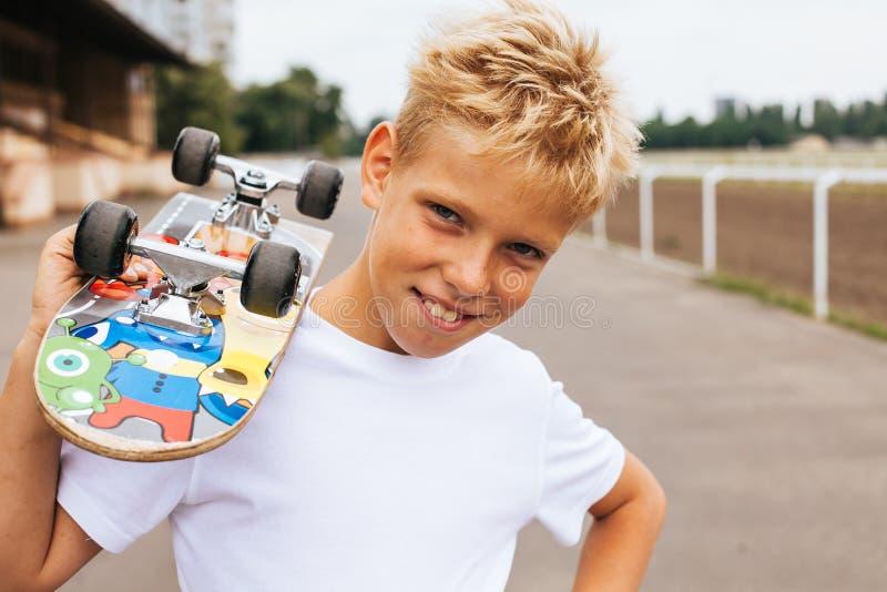 Pojkeskateboradåkare som poserar med skateboarden royaltyfri fotografi