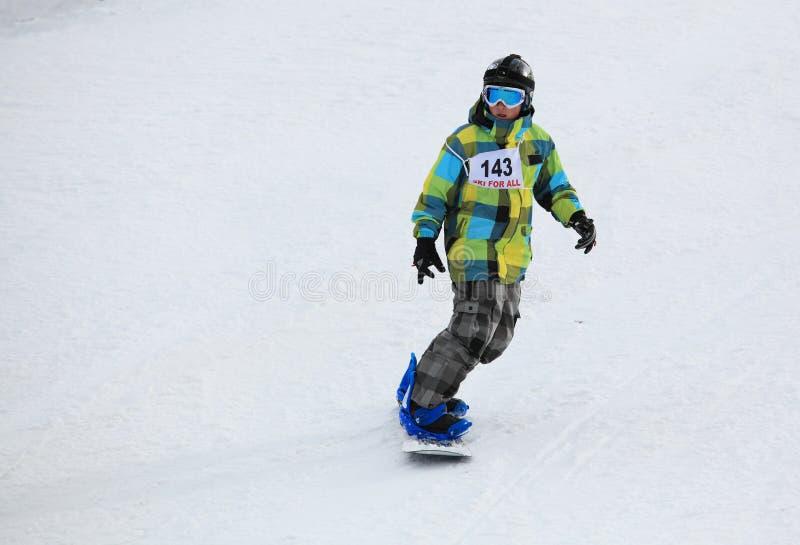 Pojkesnowboardingen skidar på sluttar arkivfoto