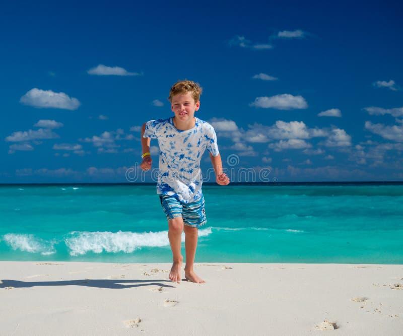 Pojkespring på strand royaltyfri bild