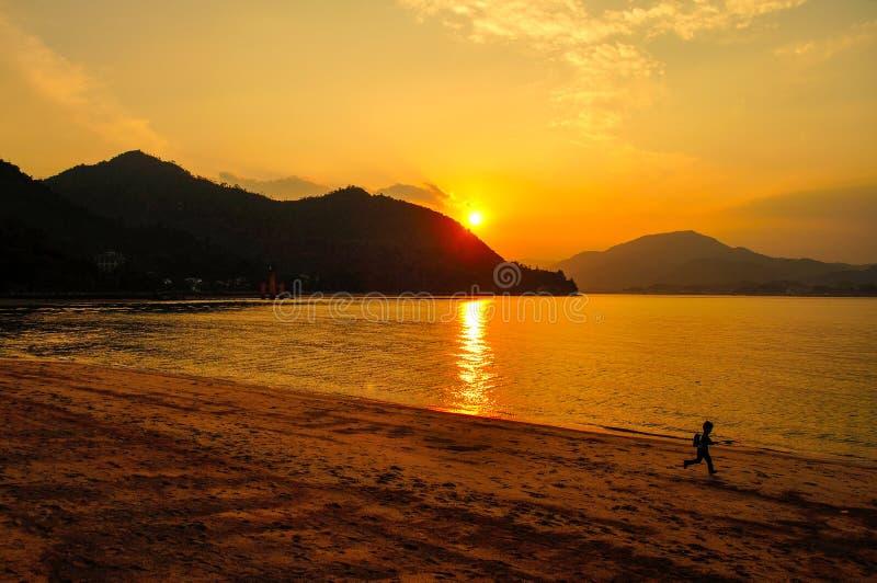 Pojkespring på stranden med inställningssolen i bakgrunden royaltyfria foton