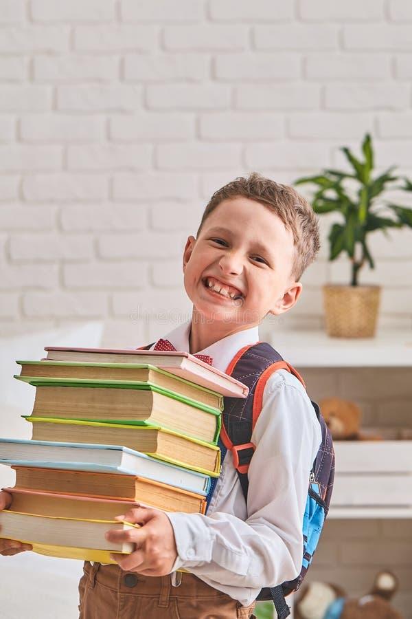 Pojkestudent som lyckligt rymmer en stor bunt av böcker och leenden royaltyfri fotografi