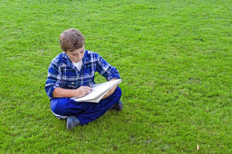 Pojketeckningen skissar på blocket arkivbild