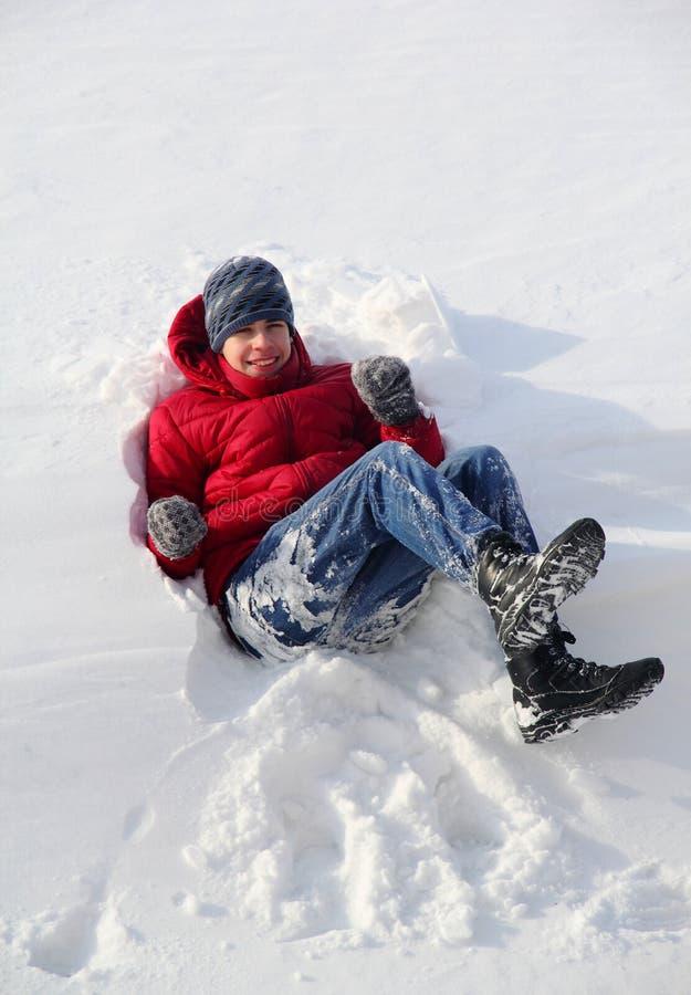 Pojketonåring som faller i snowen fotografering för bildbyråer