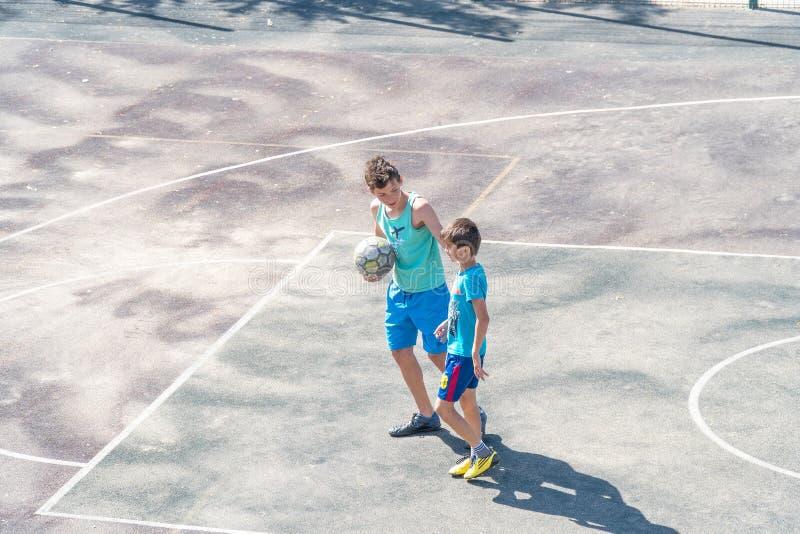 Pojketonåringar med en boll på basketdomstolen arkivfoton