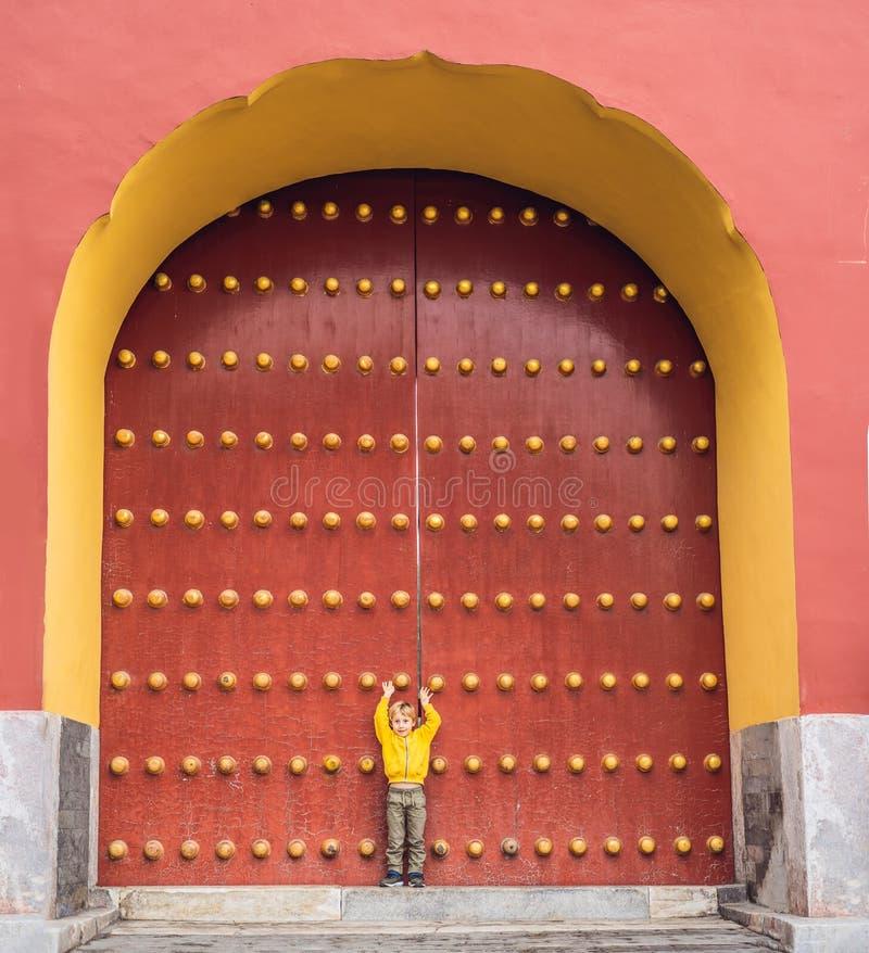 Pojketurist på bakgrunden av de stora kinesiska portarna Lopp med barn i det Kina begreppet arkivfoton