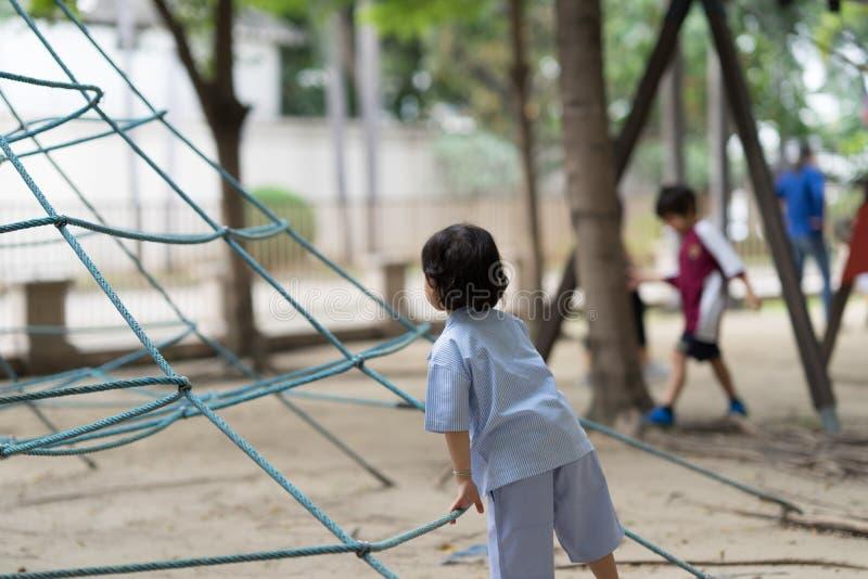 Pojkeunge i enhetlig lekroprklättring i lekplats arkivfoto