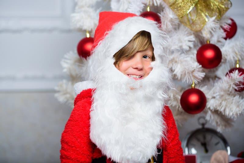 Pojkeunge som kläs som santa med det vita konstgjorda skägget och den röda hatten nära julträd JulSanta Claus dräkt för royaltyfri fotografi