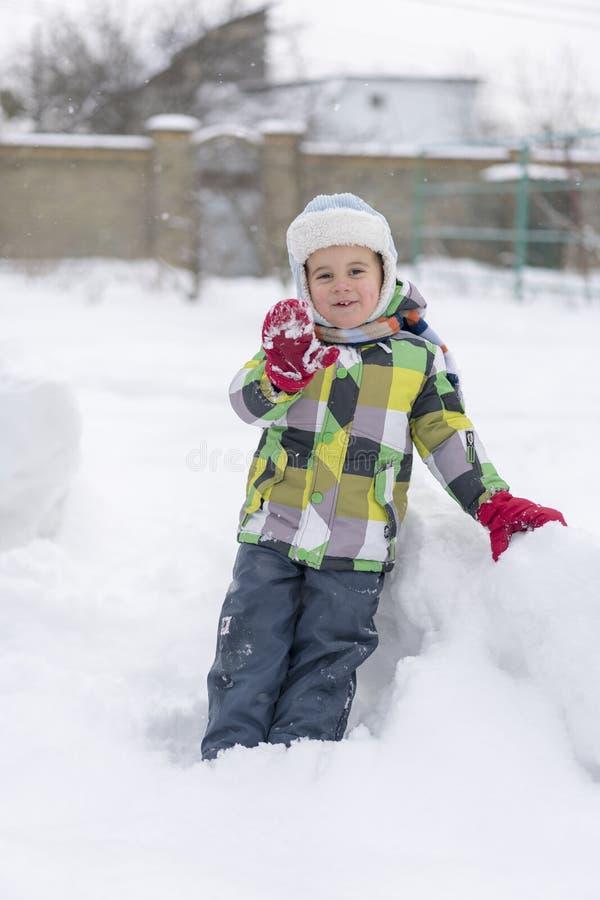 Pojkeunge som spelar i snön Behandla som ett barn att spela med insnöad vinter Liten litet barnpojke i blått omslag och färgrikt  royaltyfria bilder