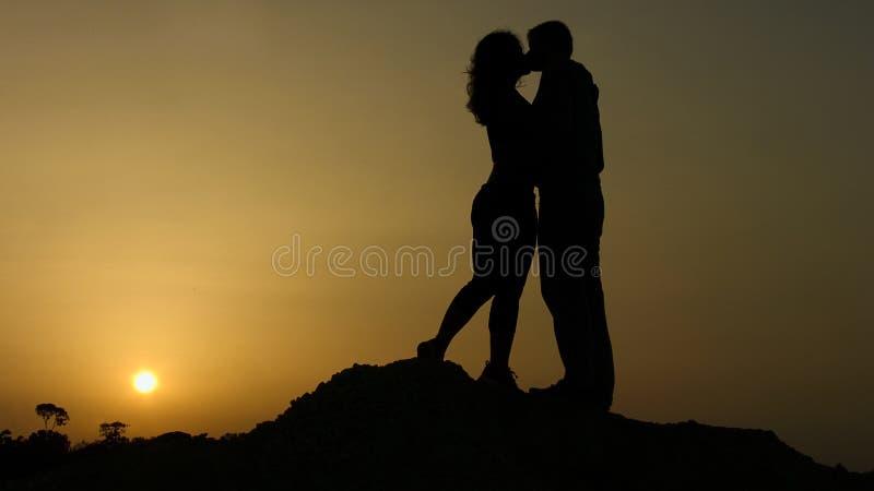 Pojkvän och flickvän som tillsammans kysser på solnedgångbakgrund, lycklig för evigt arkivfoto