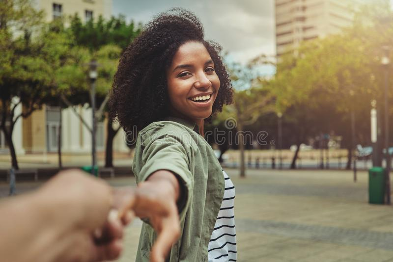 Pojkvän som följer hans lyckliga flickvän i staden arkivfoto