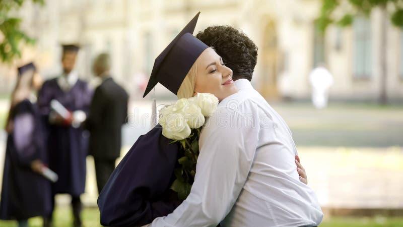 Pojkvän som ger blommor till hans doktorand- flickvän och kramar specialt tillfälle arkivfoton