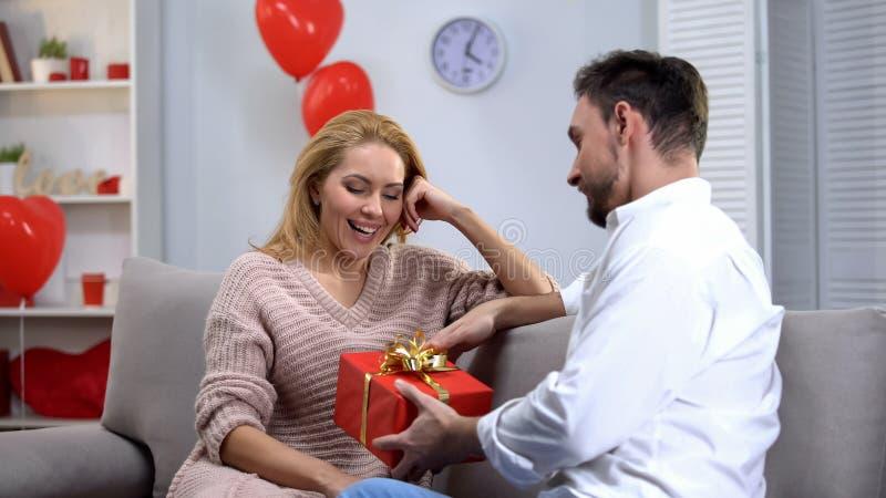 Pojkvän som ger den förvånade lyckliga damgåvan för st-valentindagen, lyckligt par arkivfoton