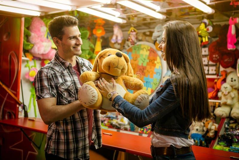 Pojkvän som ger gåva hans flickvän på nöjesfält arkivfoton