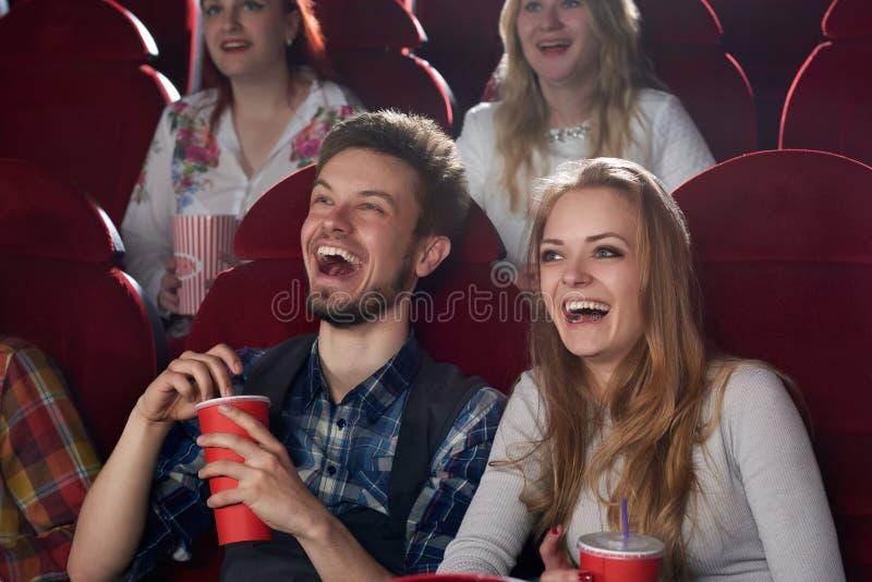 Pojkvännen och flickvännen förvånade att le hållande ögonen på komedifilm på bion royaltyfria foton