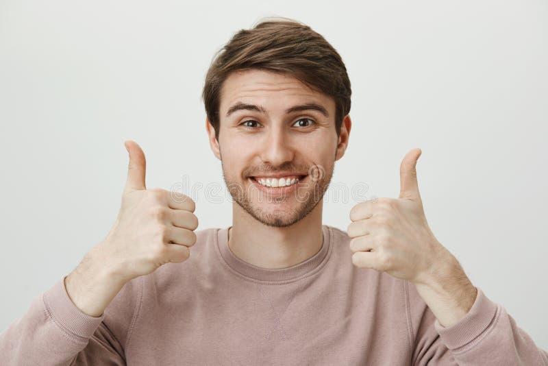 Pojkvännen stöttar flickvännen på match Lycklig attraktiv europeisk grabb med borstet i moderiktig kläder som glatt ler arkivbild