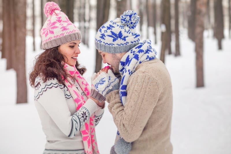 Pojkvännen värme handflickvännen som frysas i den kalla vintern, parkerar royaltyfria bilder
