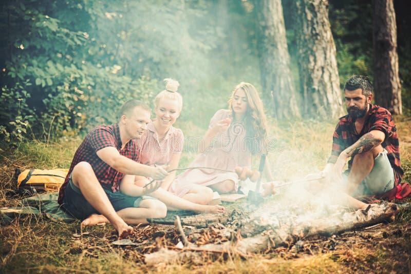 Pojkv?nner och flickv?nner tycker om campa mat Vänner har picknicken på brasan i skogmän, och kvinnor grillar på korvar arkivbilder