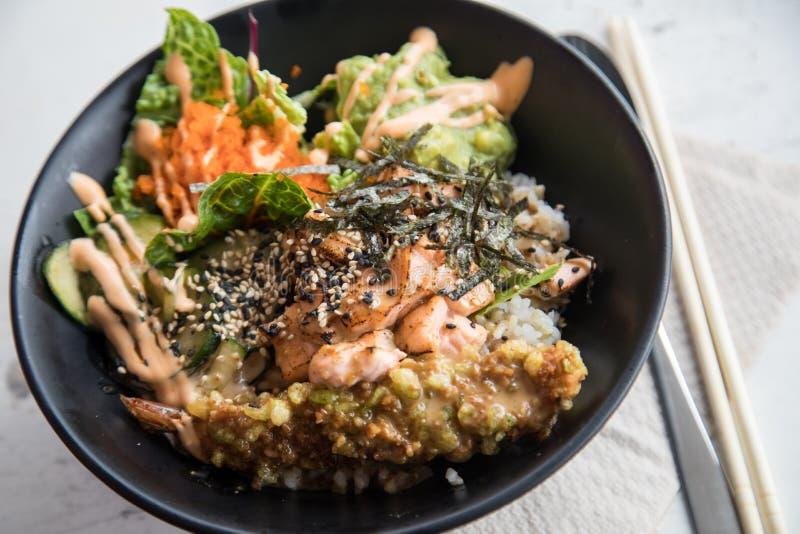 Poké-Schüssel mit flambé Lachsen, Tempuragarnele, Guacamolen, Masago-Kaviar, Salat und indischem Sesam auf Reis und schwar stockbild