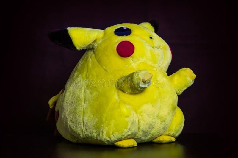 Pokémon si concentra la bambola Pikachu della peluche su fondo nero immagine stock