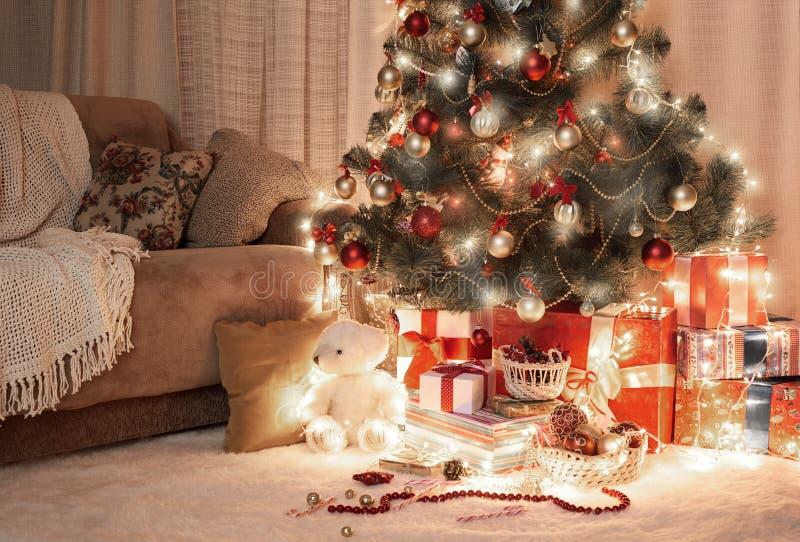 Pokój w zmroku z iluminującą choinką, dekoracja i prezenty, domowy wnętrze przy nocą obrazy stock