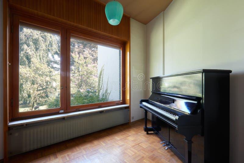 Pokój z fortepianowym i wielkim okno, mieszkania wnętrze w starym domu z ogródem obrazy stock