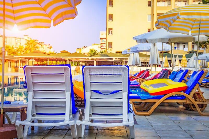 Pokładów krzesła i słońc loungers z parasolami blisko pływackiego basenu przy kurortu tropikalnym hotelem w ranku katya lata tery zdjęcia stock