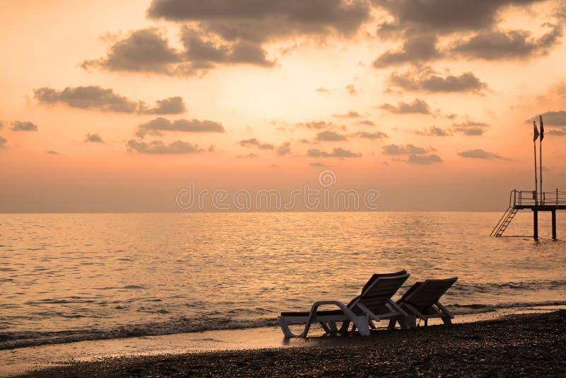 Pokładu krzesło morzem przy zmierzchem Romantyczny nastrój obraz royalty free