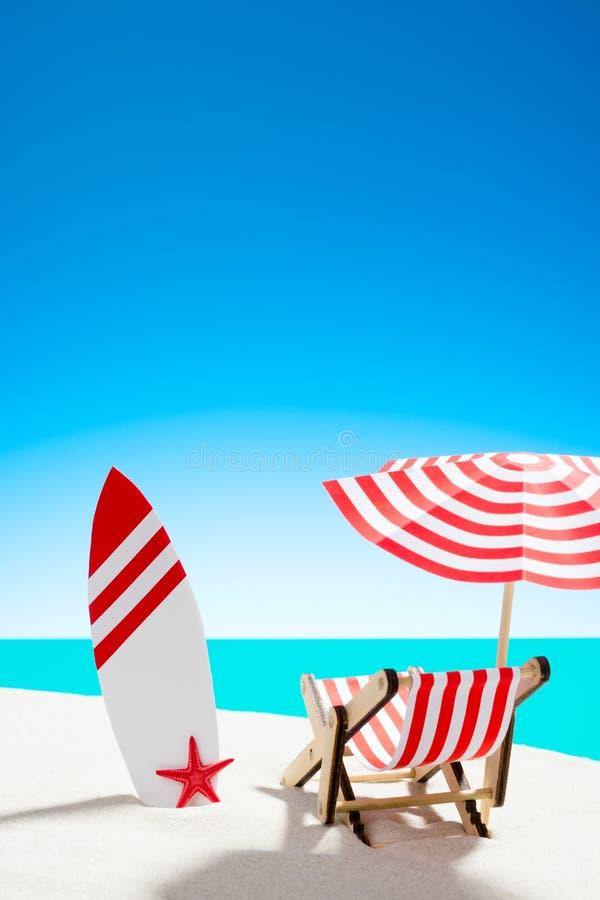 Pokładu krzesło pod parasolem z surfboard na piaskowatej plaży morzem i niebie z kopii przestrzenią zdjęcie royalty free