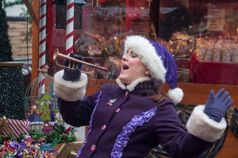 Pokazuje z parą tradycyjny muzyk i piosenkarz z purpurowym leprechaun kostiumem przy boże narodzenie rynkiem obrazy stock