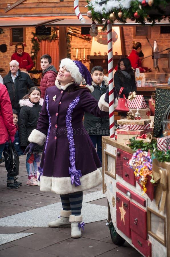 Pokazuje z parą tradycyjny muzyk i piosenkarz z purpurowym leprechaun kostiumem przy boże narodzenie rynkiem zdjęcie stock